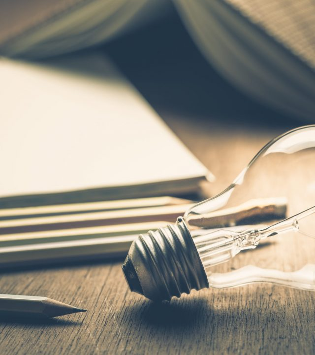 Light bulb with pencils and notebook for writing concept